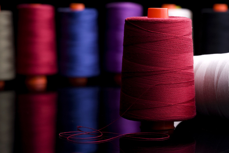 Spools of colored cotton thread, ordered composition, warm colors, red spool in the foreground with the red wire coiled in the form of elegant black table reflection, sprockets into the background blurred