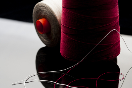 common thread, cotton yarn red and white resting on white table mirror with black shade. reel of cotton spool of red and white cotton blurred in the background