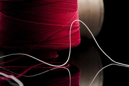 rode draad, katoenen garen rood en wit leunend op zwart tafel spiegel. reel van katoen spoel van rode en witte katoenen vaag op de achtergrond