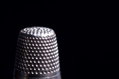 sartorial: Detail of thimble cutico on a black background
