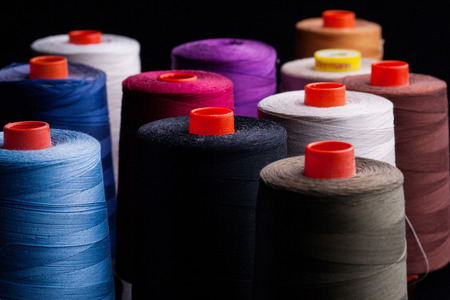 Spools of colored cotton in the group, red, blue, white, black on black background