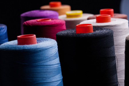 upholsterer: Spools of colored cotton in the group, red, blue, white, black on black background