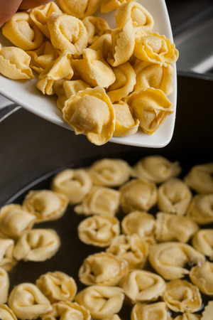 Put tortellini pasta in boiling water, kitchen in background photo