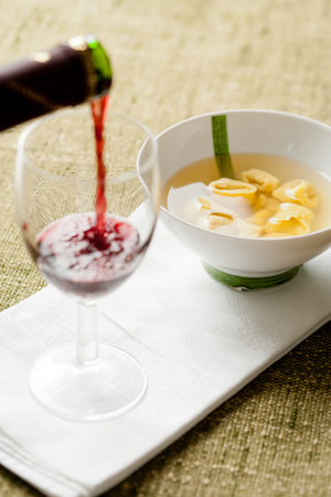 dish cloth: Pour red wine in a glass. Tortellini in broth in a white and green dish. cloth in background Stock Photo