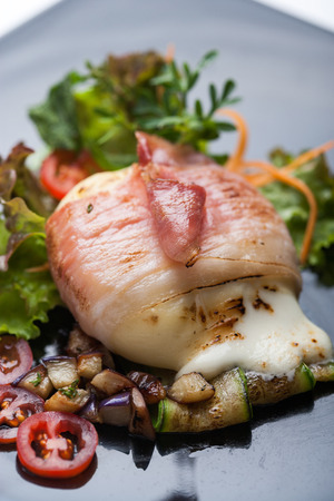 Fused cheese wrapped in crunchy bacon, grilled vegetables and salad Фото со стока