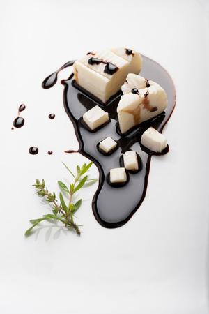 Goat cheese on aromatic vinegar on a white dish Фото со стока