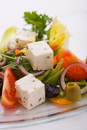 Cheese salad and fresh vegetables, olives tomatoes, lettuce, onion Фото со стока