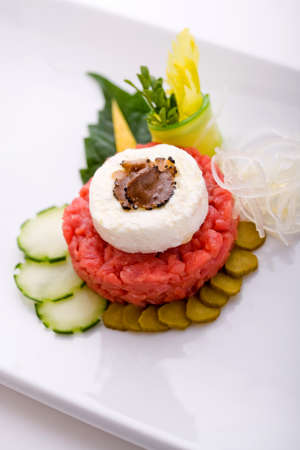 Raw meat with fresh cheese flavored with truffle and pickled gherkins