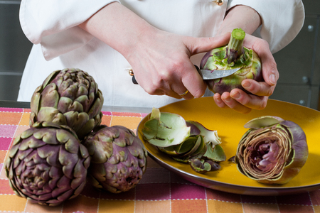 Hands clean and cut fresh Roman artichokes on a colored background Фото со стока
