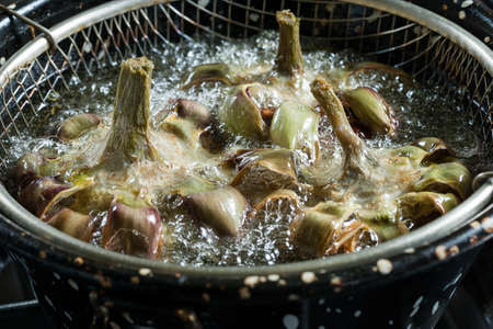 Artichokes fried in a pan of hot oil, with the grid used for frying foods. photo
