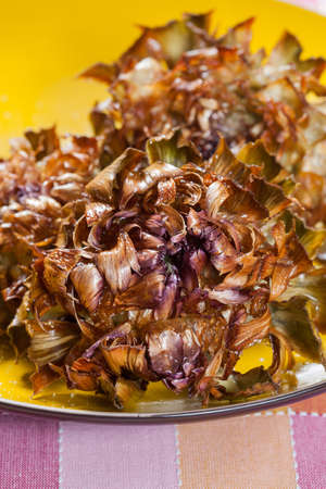 Artichokes fried in a pan of hot oil, with the grid used for frying foods. Фото со стока