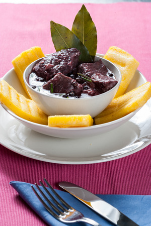 Stew meat, recipe carbonade in white bowl on white plate, white tablecloth pink meat with red wine sauce with slices of grilled polenta, rosemary and bay leaf Fogle