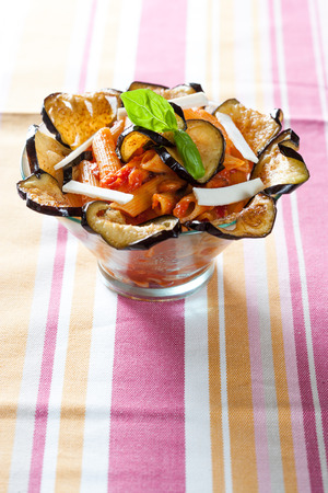 Pasta with fried eggplant, tomato and cheese, pasta alla norma, macaroni in glass bowl in the shape of flower on colorful striped tablecloth