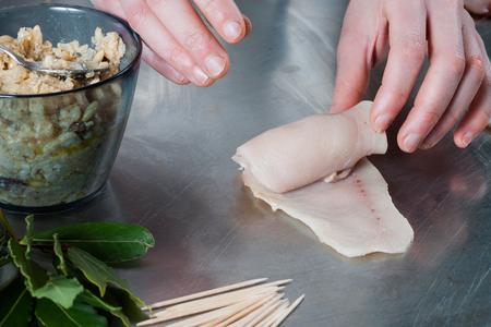 Hands preparing swordfish roulades stuffed with raisins, bread crumbs, pine nuts, bay leaves