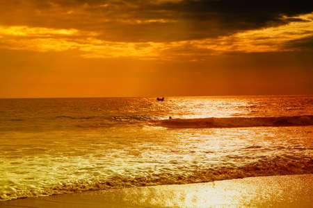 gloaming: The Indian Ocean in the gloaming of the sunset is shining in romantic warm orange and red color shades  The sea is like floodlit in liquid gold