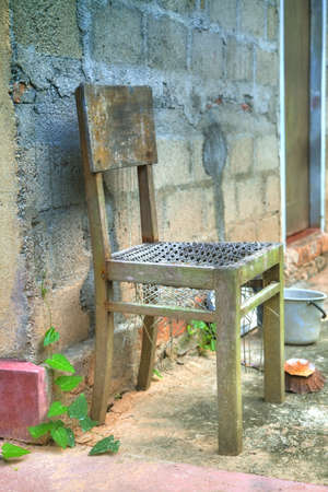 broken chair: A broken chair is standing in front of a house with a stony blue wall like an artwork Stock Photo