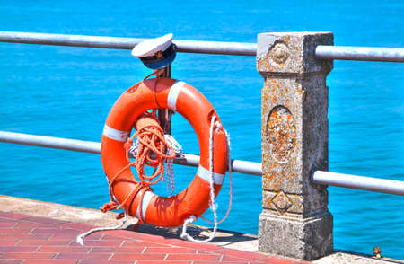 Life Belt in shining orange with a captains hat in front of a dreamful blue Lake Garda Stock Photo