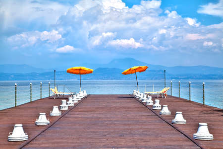 On a jetty at the Lake Garda glowing luminous orange-colored sunshades in front of a dreamful scenic