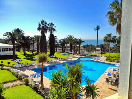 sunshades: view to a swimming pool with sunshades and palm trees