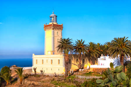 bordered: lighthouse of Tangier in the Kingdom of Morroco in West Africa in an stunning scenery with luminous blue sky at the Atlantic Ocean, bordered with date trees and cactus pears