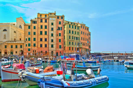 boats in the harbour of the seaport Camogli at the Italian Riviera with a gorgeous colored house facade and luminous shining blue sky