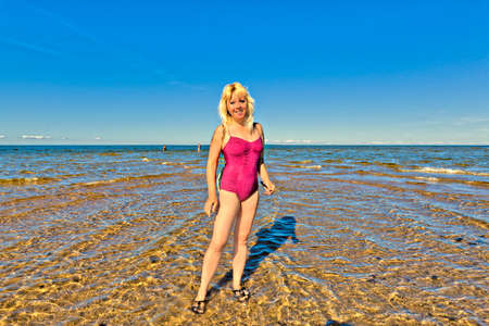 cheveux blonds: a sexy woman with blond hair and bathing wear is standing in the baltic sea by the cape kolka in latvia, where two seas are streaming together