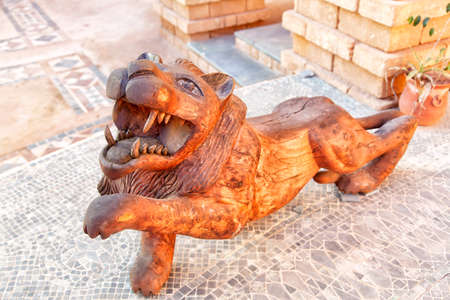 grandiose: A lion as wood sculpture is standing in an inner courtyard in the medina of the african harbor city Agadir in Morocco Stock Photo