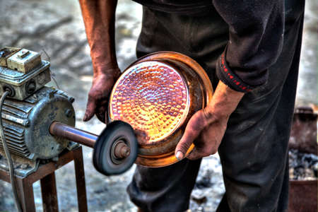 fes: A craftsman in the Kingdom City Fes in Morocco in Africa is polishing at a polishing disk a copper pot
