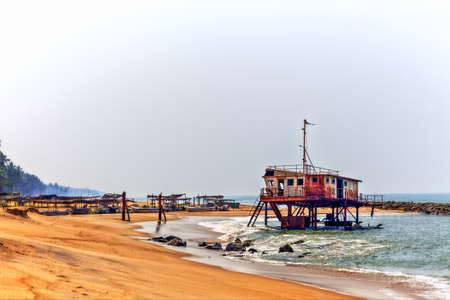 fishermans net: a rusty colorful shipwreck projects out of the water of the Indian Ocean at the coast of Sri Lanka in Asia