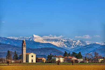 church in an idyllic little village in the North of Italy, in the background the mountains of the Karavanks in Slovenia, East Europe, and tender cotton-wool clouds