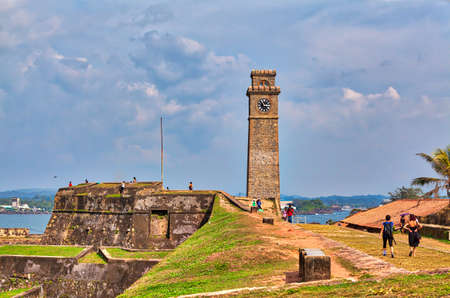 The famous clock tower in the historical Galle Fortress on the tropical island Sri Lanka in Asia in the Indian Ocean with beautiful blue sky and lots of luminous green plants