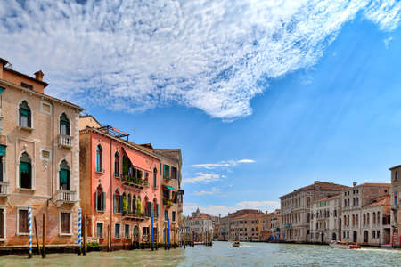 On a boat trip on the Grand Canal in the beautiful city of Venice in Italy you can see many great old historic buildings and a stunning cloudy sky Reklamní fotografie