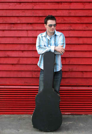 guitar case: Man leaning on his guitar case