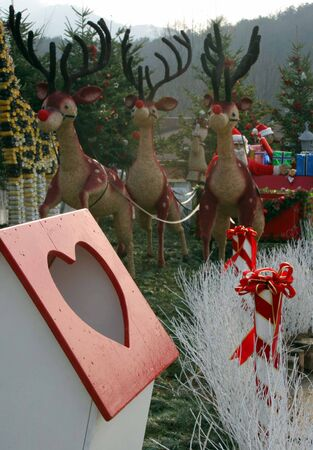 Reindeer pulling Santas sleigh towards a heart-shaped letter box photo