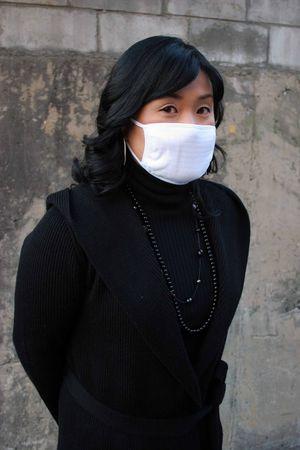 Asian woman wearing a white face mask photo