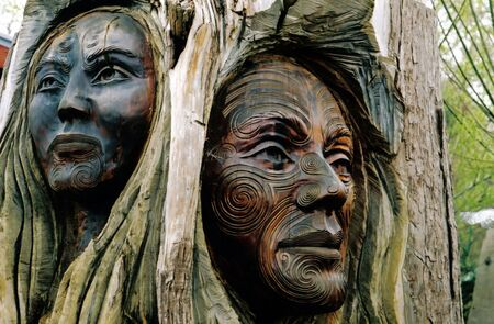 Maori carvings of a man and a womans face - New Zealand photo