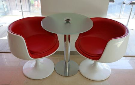 Two modern red chairs and a table photo