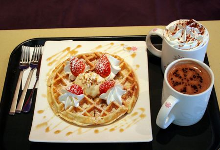 Waffle with strawberries and cream and hot chocolate photo