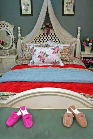 A beautiful bedroom with his and hers slippers at the foot of the bed photo