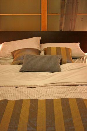Bett mit Federn und gr�n gestreiften Kissen