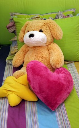 Stuffed toy and pillows on a childs bed photo
