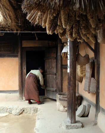 traditional house: Korean woman cleaning a traditional house at Suwon Folk Village, South Korea Stock Photo