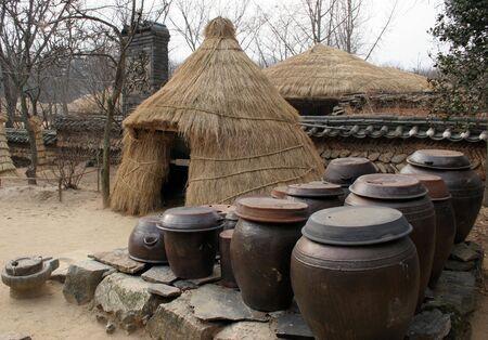 folk village: Kimchi (pickled cabbage) pots outside at straw tent at Suwon Folk Village, South Korea
