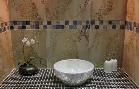Sink and flower in a luxury tiled bathroom - home interiors photo
