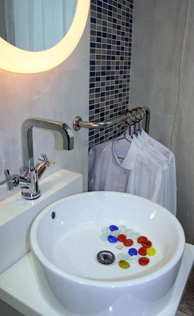 Modern bathroom with basin and shirts hanging in the background Stock Photo - 327389