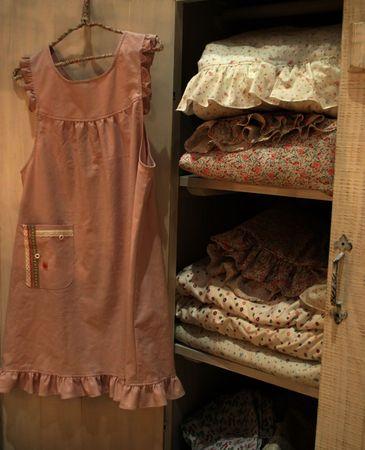 bedhead: Dress hanging on wardrobe full of linen