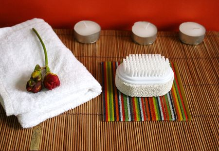 Pumice brush, candles and towel on a bamboo mat at a spa