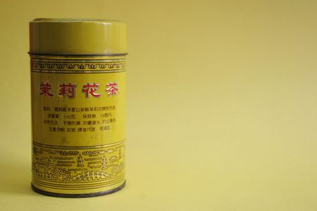 Old Chinese tea tin on yellow background - copy space  photo