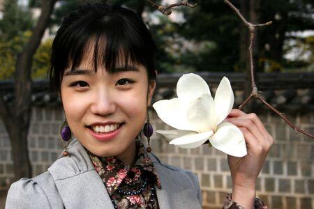 Pretty koreanischen Frau, die eine wei�e Blume Fr�hling