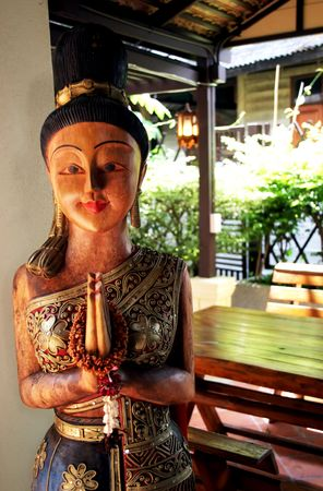 Wooden Thai statue with hands in sawasdee greeting pose photo